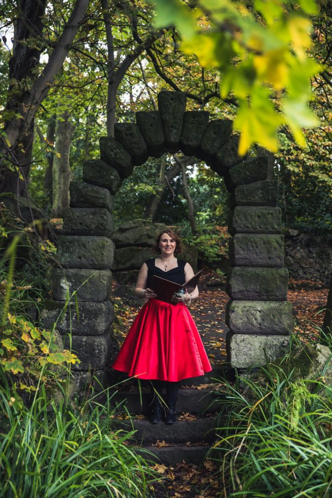 A celebrant stood under a stone archway in a wood leading an outdoor Memorial Ceremony
