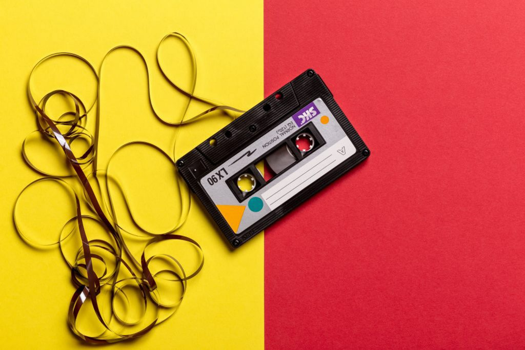 A music cassette tape sits on the middle of a red and yellow surface. The cassette is black with a white label and some of the tape has been pulled out and lies on the yellow side of the card