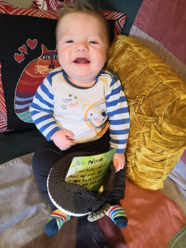 Picture of an older baby sitting on a sofa with a patchwork quilt. He likes the new website.