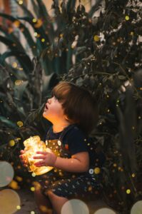 Small child crouching down but looking up. There are bushes behind him. In his hands he holds a jar with fairy lights inside. The light warms his face with a golden glow.