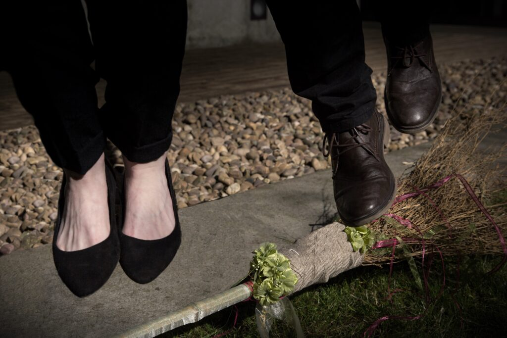 A background of pebbles, concrete and grass, a couple (we can only see their feet) jump over a decorated traditional twig broom or besom. This is a mini ceremony called Jumping the Broom.