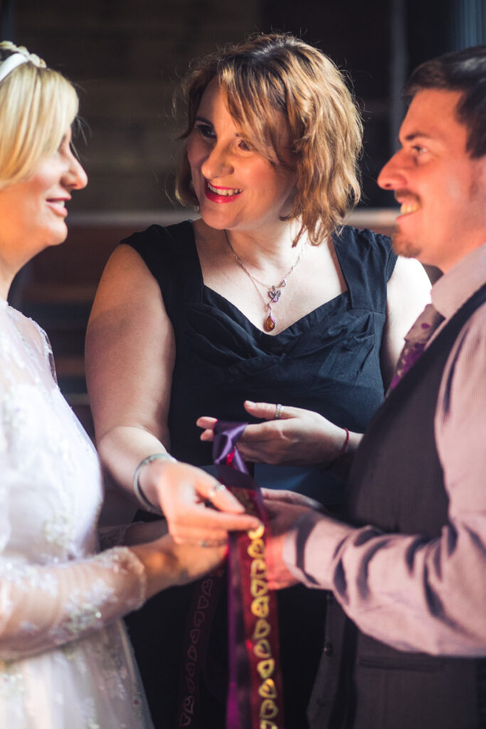 Bride is facing groom with Celebrant in the middle. The celebrant is wrapping ribbons around the bride and groom's hands in a mini ceremony known as the handfasting ceremony.