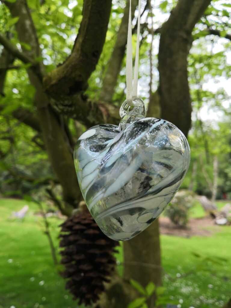 In the foreground, a glass heart hanging from a white ribbon. In the background, a fir cone and tree with grass.