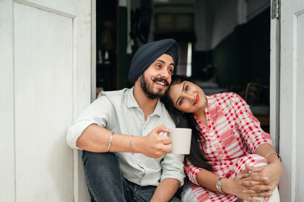 A couple sat together on the steps of their home. He is wearing a turban and has a beard and moustache and holds a white cup in his hand. She has her head on his shoulder and is wearing a red and white checked top. Both are smiling.
