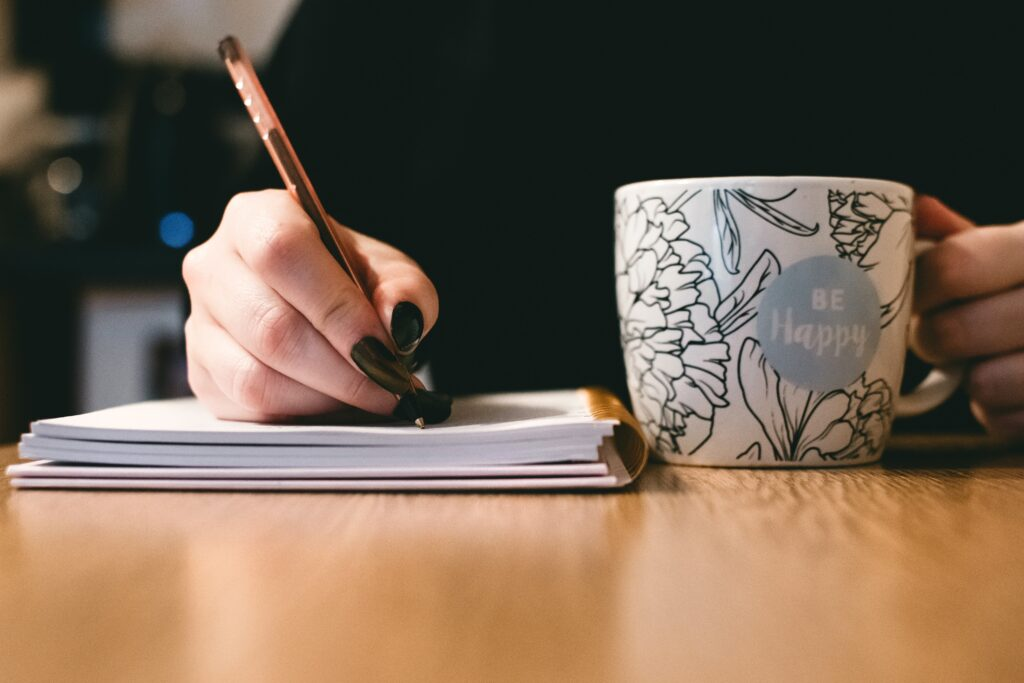 You can see a woman's hands with black nail varnish. One hand holds a cup with Be Happy and flowers on it. The other hand is holding a biro and writing wedding vows in a spiral bound notebook.