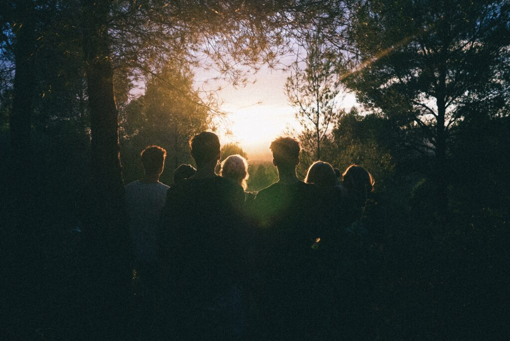 A group having a quiet moment of reflection in a wood as the sun comes up at a Memorial Ceremony