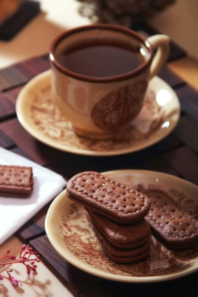 In the foreground are chocolate biscuits on a cream and brown patterned plate. Behind that toward the back of the picture is a similarly patterned cup and saucer with tea to go with the biscuits as a reward for reading How much is a Celebrant Wedding Ceremony?