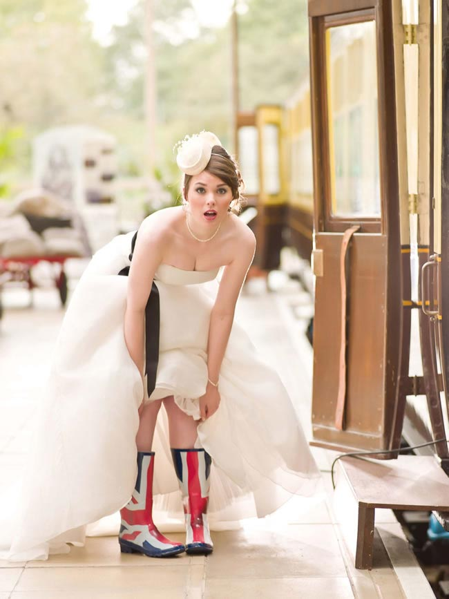 Woman in old style train station. She is in a wedding dress and is bending over. Her dress is pulled up to the knee at the front to show off her Union Jack wellies to highlight Brit Weddings.