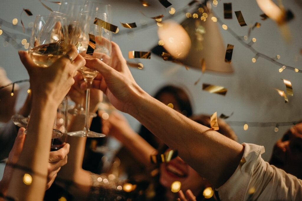 Several people raising wine glasses - you can only see arms - with white wine in while short gold slips of foil fall around them as they celebrate Celebrant Brit Weddings