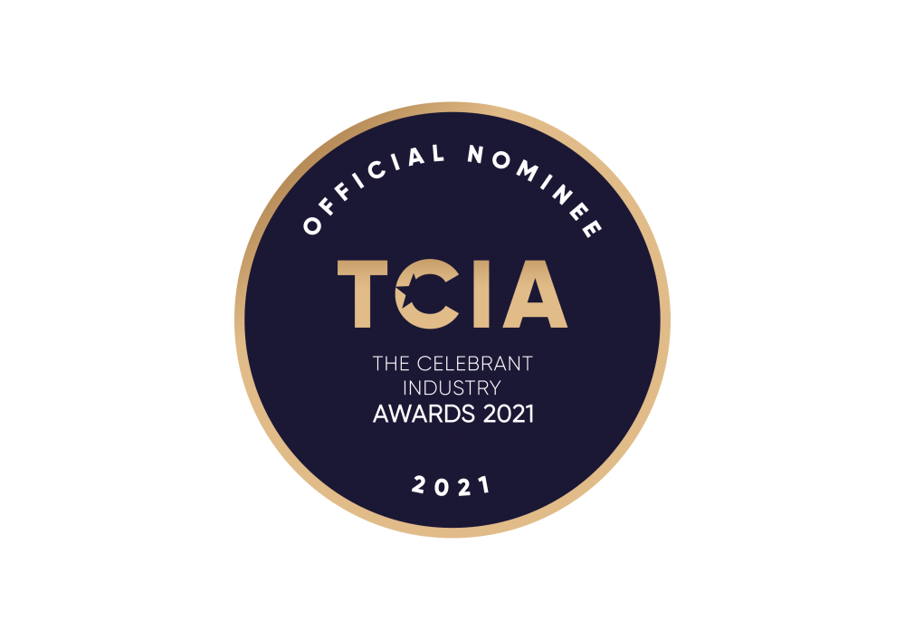 A round logo with gold border and dark navy blue background. In white writing around the top, Official Nominee. In the centre in gold writing TCIA and underneath in small white writing The Celebrant Industry Awards 2021. An dat the bottom in white is 2021. All this because Sarah Nelson has been nominated for an award.