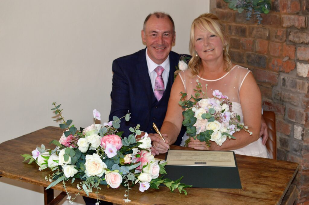 Bride and Groom sitting at a table signing a wedding certificate.