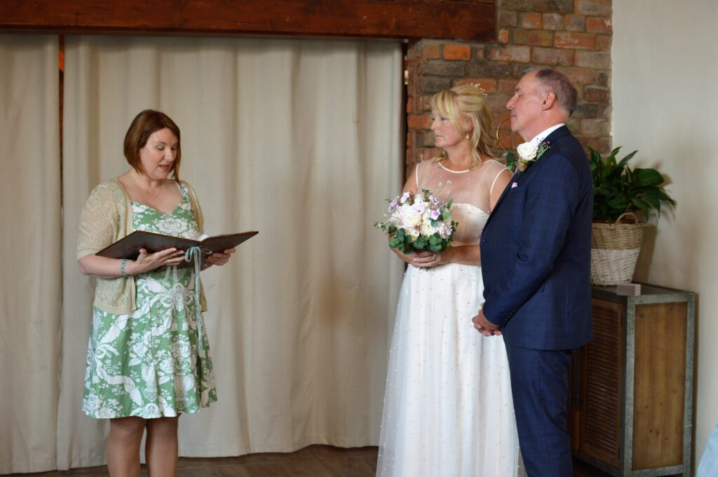 Celebrant, left of picture, conducting wedding ceremony with bride and groom right of picture.