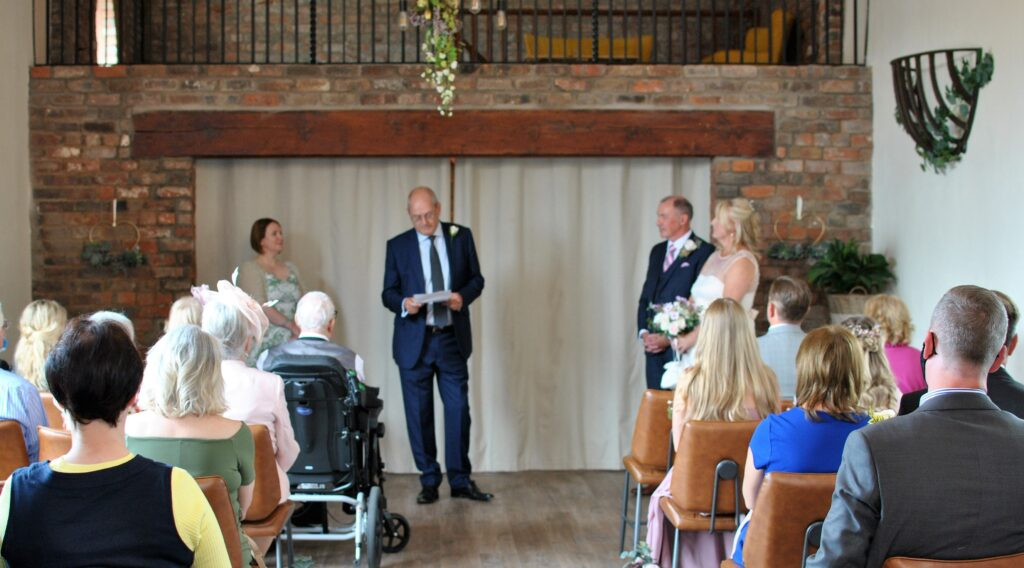 Guests at PB and GM's wedding  listening to a guest reading a poem with the bride and groom to the right of the picture and Celebrant Sarah Nelson to the left